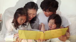Family reading a book as they sit together Footage
