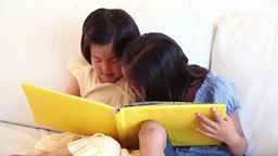 Girl talking to her sister as they read a book tog Footage