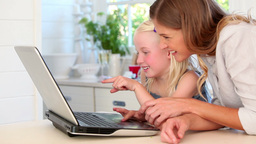 Mother and daughter laughing as they use a laptop Footage