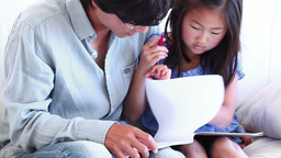 Father helping his daughter to do her homework Footage