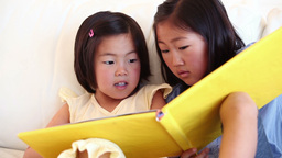 Two girls reading a book together Footage