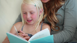 Girl reading a book with her mother Footage