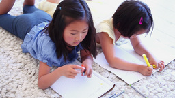 Two girls colouring while lying next to each other Footage