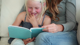 Girl laughing as she is reading a book with her mo Footage