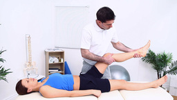 The leg of a woman being stretched by a physiother Footage