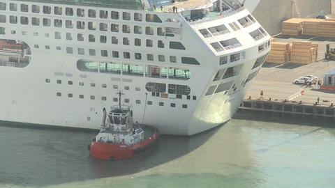 tug pushs cruise liner into berth time lapse Footage