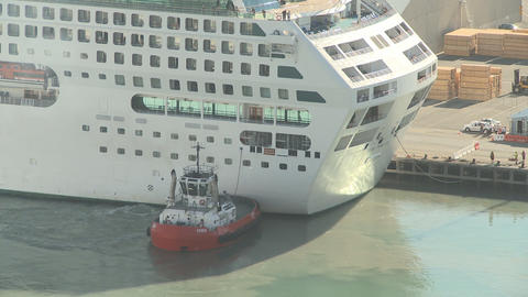 tug pushs cruise liner into berth time lapse Stock Video Footage