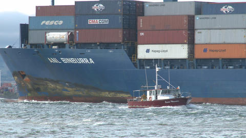 container ship and fishing boat pass bow Stock Video Footage