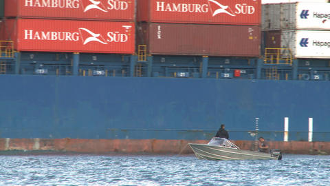 small boat and a big container ships stern Stock Video Footage