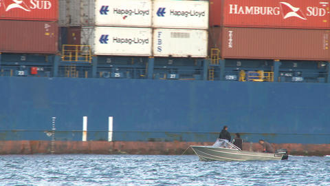 small boat and a big container ships stern Footage