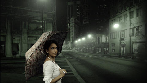 Young woman holding umbrella in snowy street Stock Video Footage