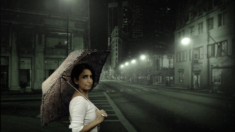 Young woman holding umbrella in snowy street Footage