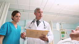 Medical team talking with a patient in a bed ward Footage