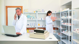 Pharmacist Talking On The Phone In A Pharmacy With stock footage