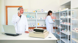 Pharmacist Talking On The Phone In A Pharmacy Whil stock footage