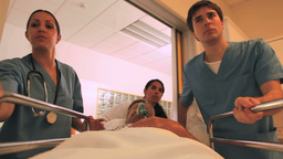 Nurses driving a patient on his bed with an oxygen Footage
