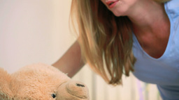 Smiling woman giving a teddy bear to a smiling girl in a bed Stock Video Footage