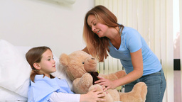 Smiling woman while giving a teddy bear to a girl in a bed Live Action
