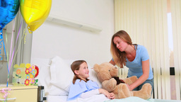 Smiling woman giving a teddy bear to a smiling girl in a bed Footage