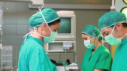 Side view of a surgical team operating Footage