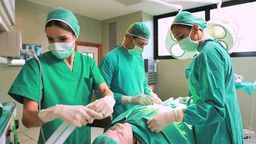 Surgeon And A Team Operating A Patient While Check stock footage