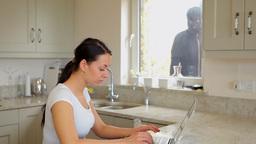 Burglar watching woman through window and then goi Footage
