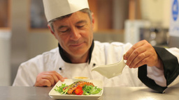 Smiling chef pouring dressing over salmon dish Footage