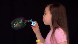 Cheerful girl making big bubbles Footage