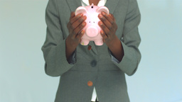 Businesswoman shaking coins out of piggy bank Footage