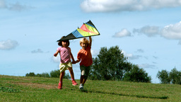 Little boy and little girl playing with kite Footage