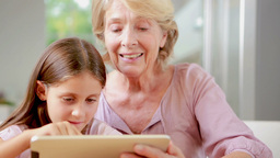 Child using tablet with her granny Footage