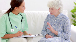 Elderly Woman Telling Home Nurse About Back Pain stock footage
