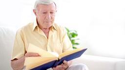Old man looking through photo album Stock Video Footage