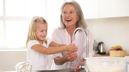 Happy grandmother and granddaughter washing hands Footage
