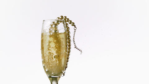 String of pearls falling into champagne glass Footage