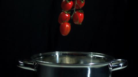 Vine tomatoes falling into saucepan Footage