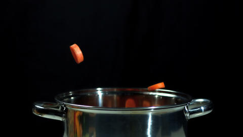 Chopped carrots falling into pot Footage