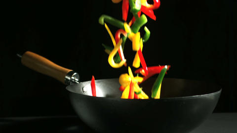 Mixed sliced peppers falling into wok Footage