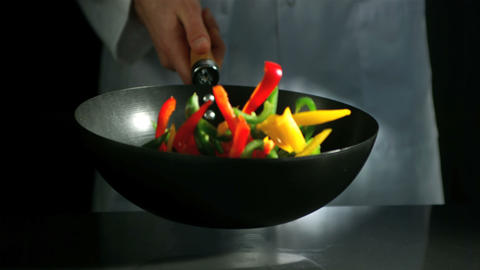 Chef tossing wok of sliced peppers ビデオ