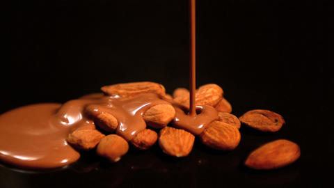 Melted chocolate pouring over almonds Footage