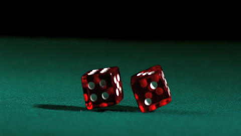 Red dice falling and bouncing on green table Footage