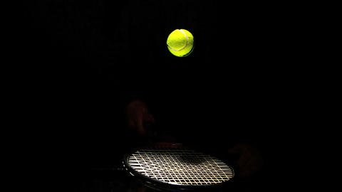 Tennis ball bouncing on a racket on black background Live Action