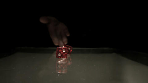 Hand throwing two red dice onto table Footage