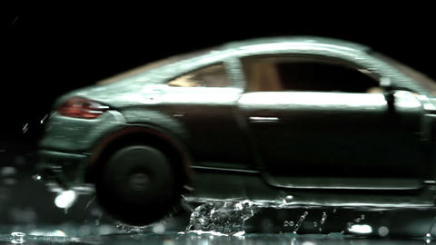 Green toy car rolling over puddle and splashing wa Footage