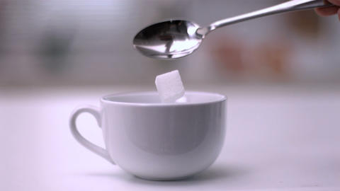 Sugar cube falling from teaspoon into a white cup Footage