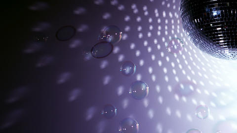 Shiny disco ball revolving with floating bubbles c Footage