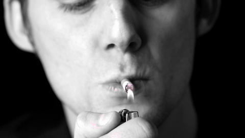 Man lighting up a cigarette in black and white Footage