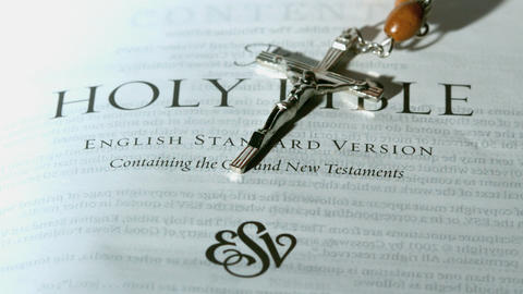 Rosary beads falling onto first page of the holy b Footage