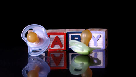 Pacifiers falling in front of blocks spelling baby Footage