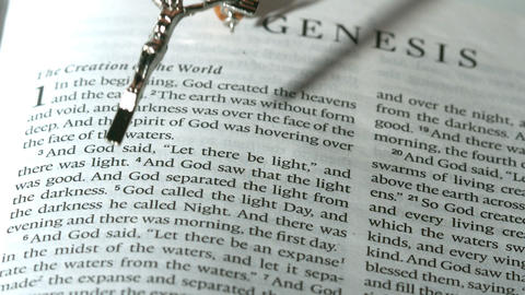 Rosary beads falling onto the book of genesis Footage